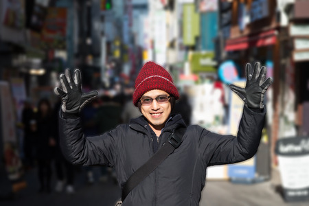 Asian male in red winter hat in jacket raise hands backpack traveler around city