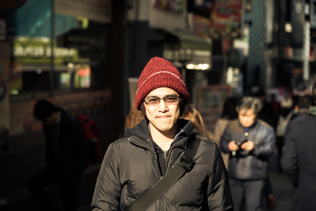 casual wear: Asian male in winter hat in jacket stand around city with smile and relax expression