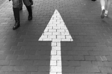caminando: Flecha recta en el pavimento a pie de calle, con la gente que recorre usar jeans moda vintage en blanco y negro