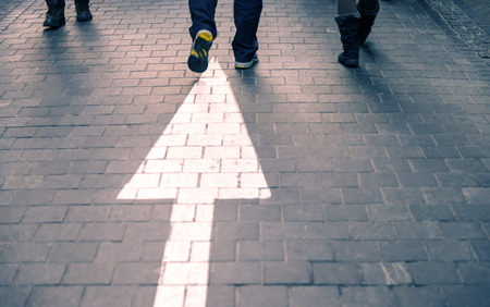 bodyparts: White arrow straight on pavement walking street with walking people with yellow shoes purple vintage