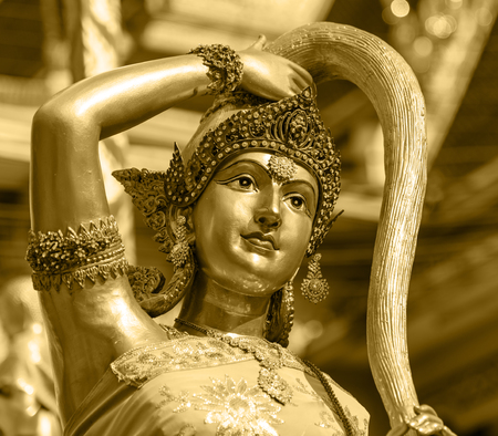 Earth goddess bronze statue  closeup on face in Thai style temple same concept as mother earth named Gaia in Greek mythology golden vintage tone