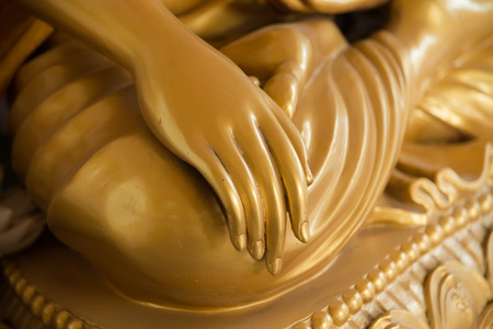 buddha hand: Golden Buddha hand on knee of statue closeup Stock Photo