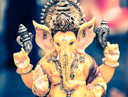 parvati: Yellow Ganesh Elephant Hindu god statue closeup focused for rich and break the obstacle in life pose Stock Photo