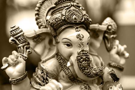 ganapati: Yellow rasin Ganesh Elephant god statue closeup focused on face  sepia tone Stock Photo