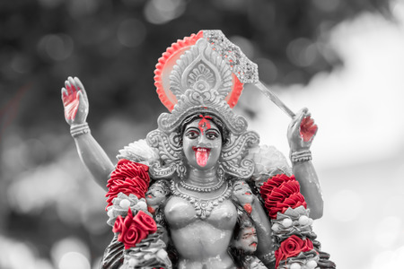 Maha Kali : The goddess of Hindusim statue hold the head of asura  with flower decoration and show her tongue with blood split red tone