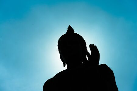 statue: Buddha statue with dark silhouette with sunlight in evening with deep blue sky