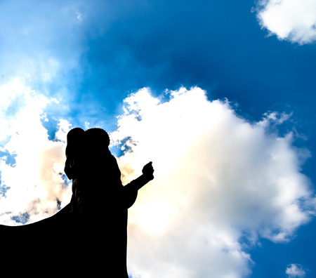 mediate: Buddha statue ok sign post bottom view with dark silhouette with deep clear blue sky with few clouds and white light glowing