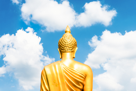 Big Buddha: Golden Buddha statu e from back focused on head  on white cloudy blue sky in sunny day