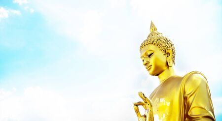 buddha hand: Golden buddha hand on O.K. sign (peace) with blue sky and clouds closeup focused on  hand side view