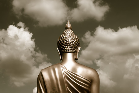 Golden Buddha statue from back focused on head  sepia tone