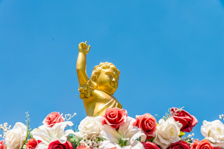 prince of peace: Golden baby Buddha statue raise arm and point forefinger up to blue sky pose