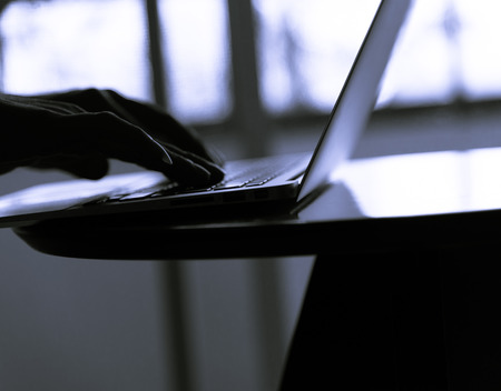 netbook: Silhouette blur  of human hand  use slim notebook (like netbook) on table in the room cool blue tone Stock Photo