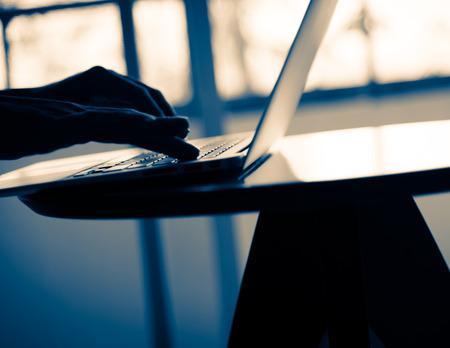 netbook: Silhouette blur  of human hand  use slim notebook (like netbook) on table in the room split-tone vintage