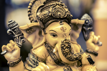 Yellow rasin Ganesh Elephant god statue closeup focused on face vintage tone Stock Photo