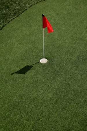 well manicured putting green with red flag Stok Fotoğraf