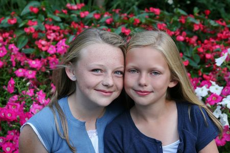 two blonde sisters surrounded by flowers
