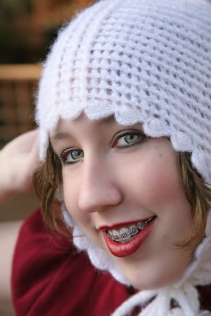 crooked teeth: teenage girl with braces and a hat