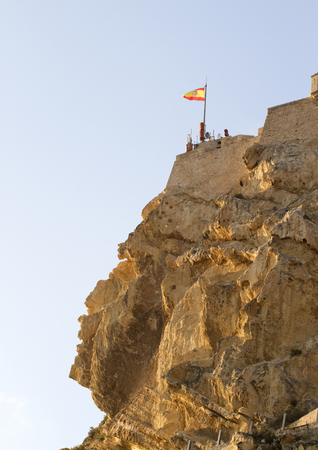 spanish looking: Alicante castle over the mountain Benacantil it is Known as muslim face looking to sky. Spanish flag on the top
