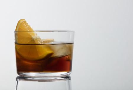 clásico vaso de vermut rojo con hielo y rodaja de naranja sobre un fondo blanco con una hermosa reflexión Foto de archivo