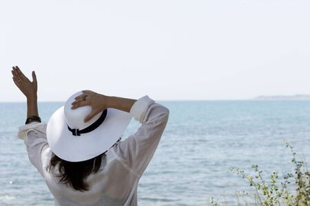 girl waving in front of the Mediterranean sea with an oversizing straw white hat
