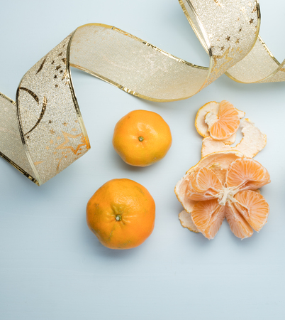 mandarins on a blue table, one of them open showing its freshness, on the left side a christmas ribbon