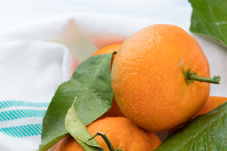 fresh mandarins on a white napkin with green bars.