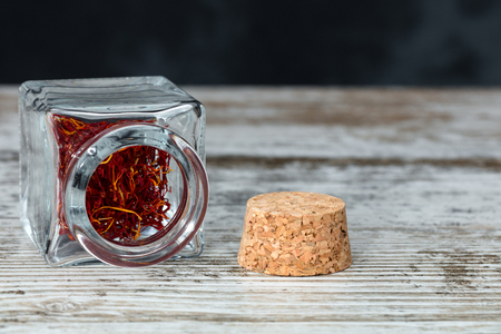 saffron threads inside a small glass jar opened on a wooden table close to the cork