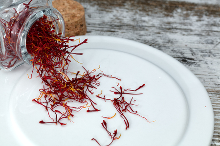 saffron threads on a plate, comming from a small glass jar