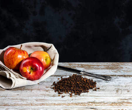 recipe with cloves and apple on an old wooden white table. Non uniform dark background with free space for text