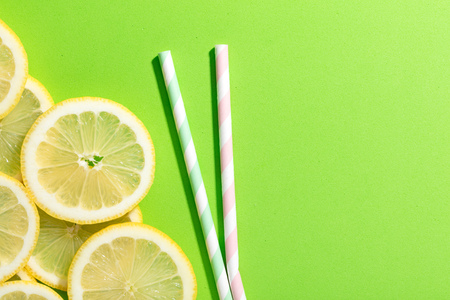 slices of lemon on green colored background with two striped straw Imagens