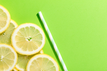 slices of lemon on green colored background with an striped straw Imagens