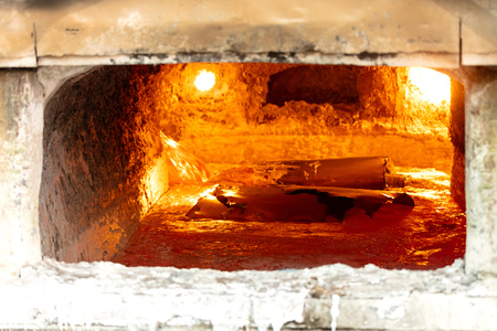 looking inside an aluminum melting furnace, in a foundry, with liquid and solid pieces of metal