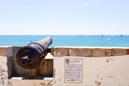 former cannon in Sitges village with ships sailing in the horizon on a blue sea