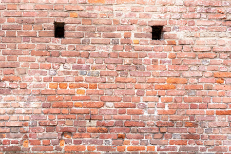red adobe bricks wall background, with two vent holes