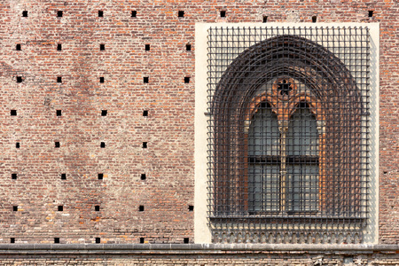 detail of a renaissance window with a pointed arch, in Sforza castle of Milan, with the wall made of adobe bricks 新闻类图片