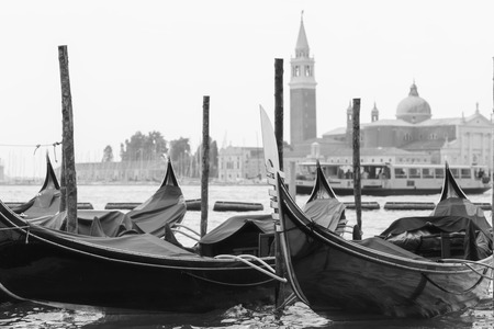 gondolas moored to the poles in the foreground and the church of San Giorgio Maggiore in the background, black and white photography with a winter atmosphere