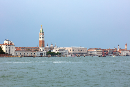 San Marcos square in Venice, seen from the sea with hundreds of tourist walking on the edge of the lagoon Imagens