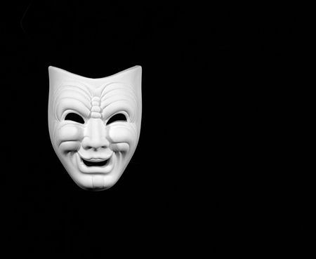 theatre mask expresing the comedy, white mask on black background with free space for text