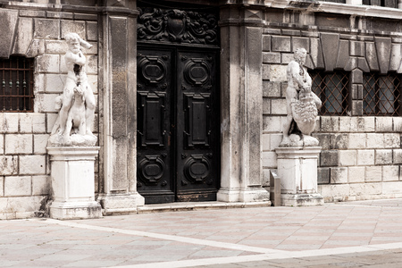 black door in the exterior of an old building with white marble stones and two statues on the sides