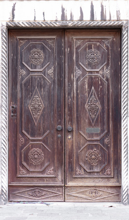 wooden brown venetian door on white stones wall, it seems old and ornamented 免版税图像