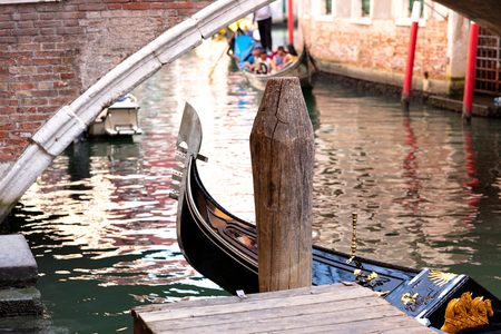 gondola docking at the pier with a bridge in the background and another gondola navigating with tourists 免版税图像