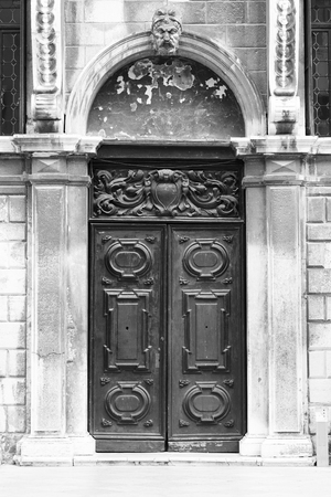 black door in the exterior of an old building with white marble stones and two statues on the sides, black and white photography