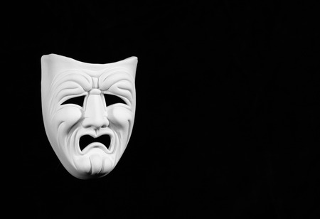theatre mask expresing the tragedy, white mask on black background with free space for text