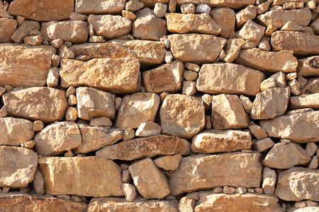 wall of yellow irregular stone blocks with various sizes