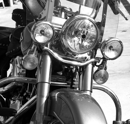 three headlights of a large classic motorbike with metal chrome, parked, black and white photo