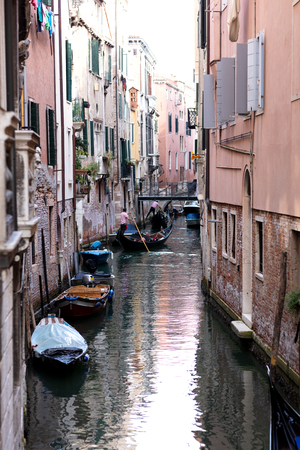 narrow canal in Venice with boats stracked to the sides and two gondolas in the background navigating