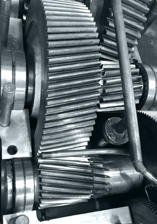 large gearbox open, showing the gears, the whole set into the iron box, industrial environment, photo in black and white with bluish tone