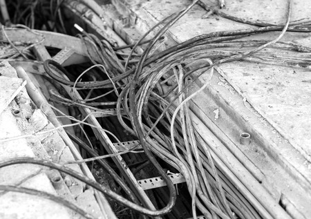electric cable duct open, showing different thickness, with a dirty appearance in an industrial environment, waiting to be removed. Black and white photo 免版税图像