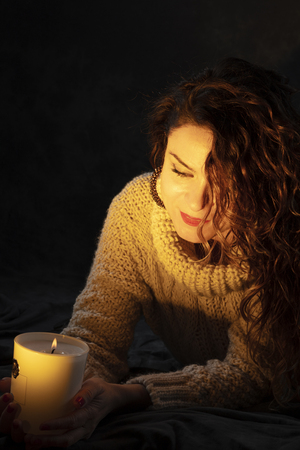 young girl holding a candle with the glow of the bonfire on her face. The expression reflects happiness and hope