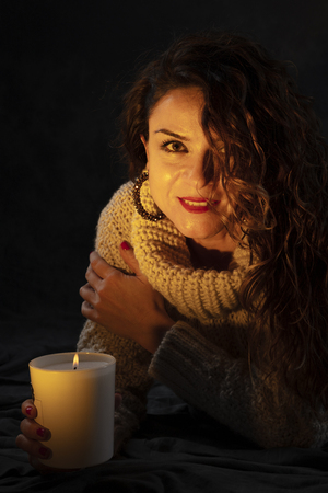 young girl holding a candle with the glow of the bonfire on her face. The expression reflects happiness and hope, she is looking at the camera